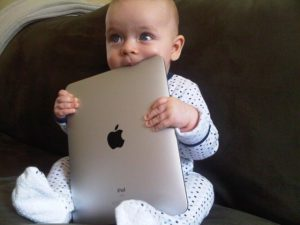 photograph of a baby chewing on an ipad