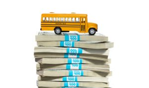 School bus sitting on a stack of cash